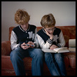 Two boys wearing identical jackets cell phone book
